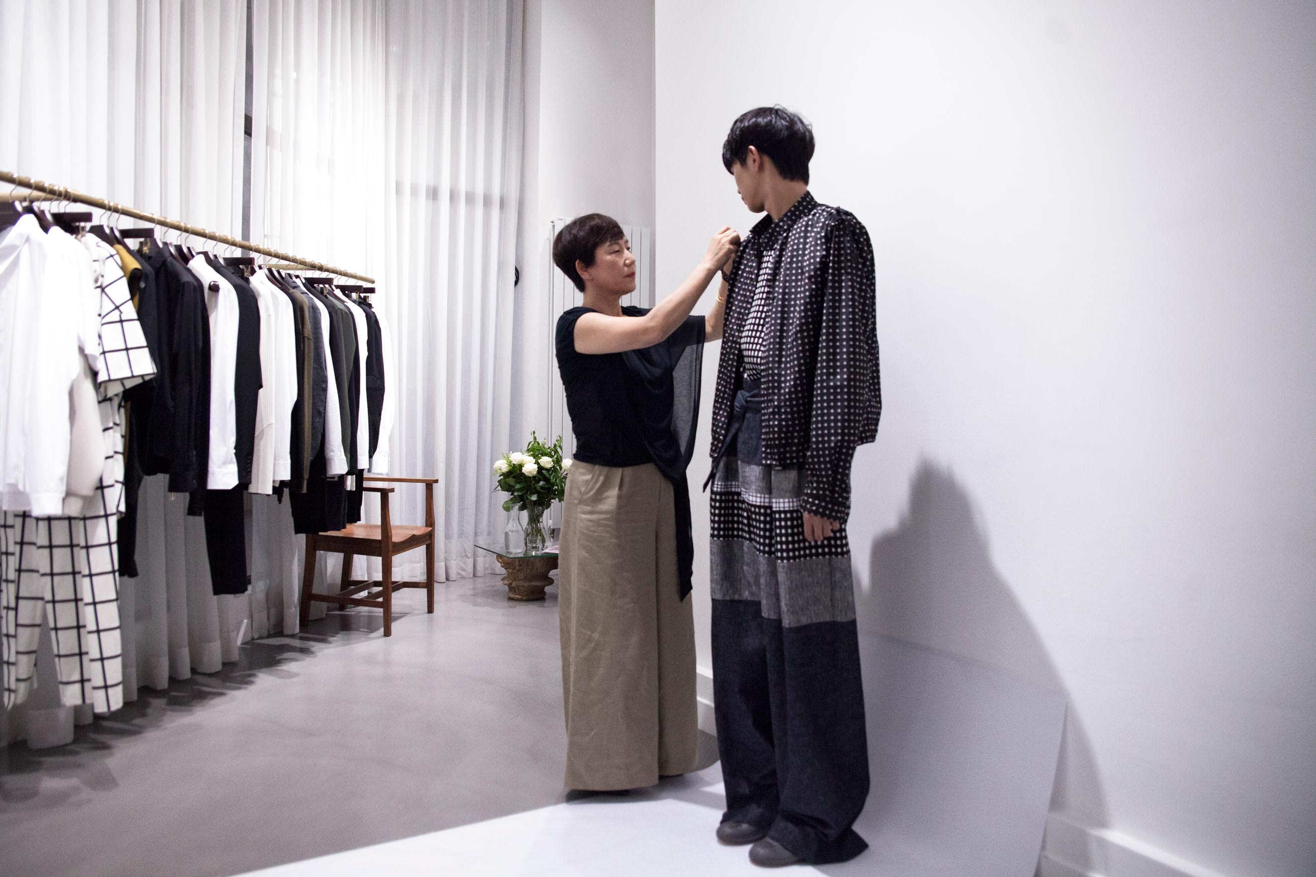 """Mme Woo dans son showroom du Maraisquelques jours avant le défilé Wooyoungmi printemps-été 2017. Photo : Mehdi Mendas   Née en Corée en 1959, Mme Woo entame des études de mode à l'université de Séoul en 1978. Elle gagne dès 1983 le prix de la mode international d'Osaka. Après avoir créé sa première maque de prêt-à-porter masculine en 1988, elle devient l'un des membres phares de la plate-forme coréenne de jeunes créateurs """"New Wave"""" dans les années 90. En 2002, elle lance Wooyoungmi dont le défilé s'est imposé comme un incontournable de la Fashion Week parisienne. Rencontre à l'occasion du défilé printemps-été 2017 fin juin à Paris.   Numéro : Pourquoi vous inspirer de l'artiste Sol LeWitt pour votre collection printemps-été 2017 ? Mme Woo :Avant de penser aux thèmes de la collection, je réfléchis toujours à un type d'hommes en particulier. Un homme idéal: élégant et sensible à l'art. Je suis par ailleurs fascinée par les wall drawings [dessins monumentaux sur mur]de Sol LeWitt, à la fois très masculins par leuraspectgraphique, et minimalistes et doux dans leur forme. Il m'est apparu comme une évidence que l'on pouvait réunir cet homme élégant et ces œuvres délicates. Quand vous regardez de près certains de ces dessins, vous découvrez des lignes qui se joignent et qui se détachent, se réfractent et se répètent avec une précision mathématique, une très bellerégularité, comme un chaos ordonné. J'ai cherché à réinterpréter les motifs et ce qu'ils inspirent aveccette nouvelle collection."""