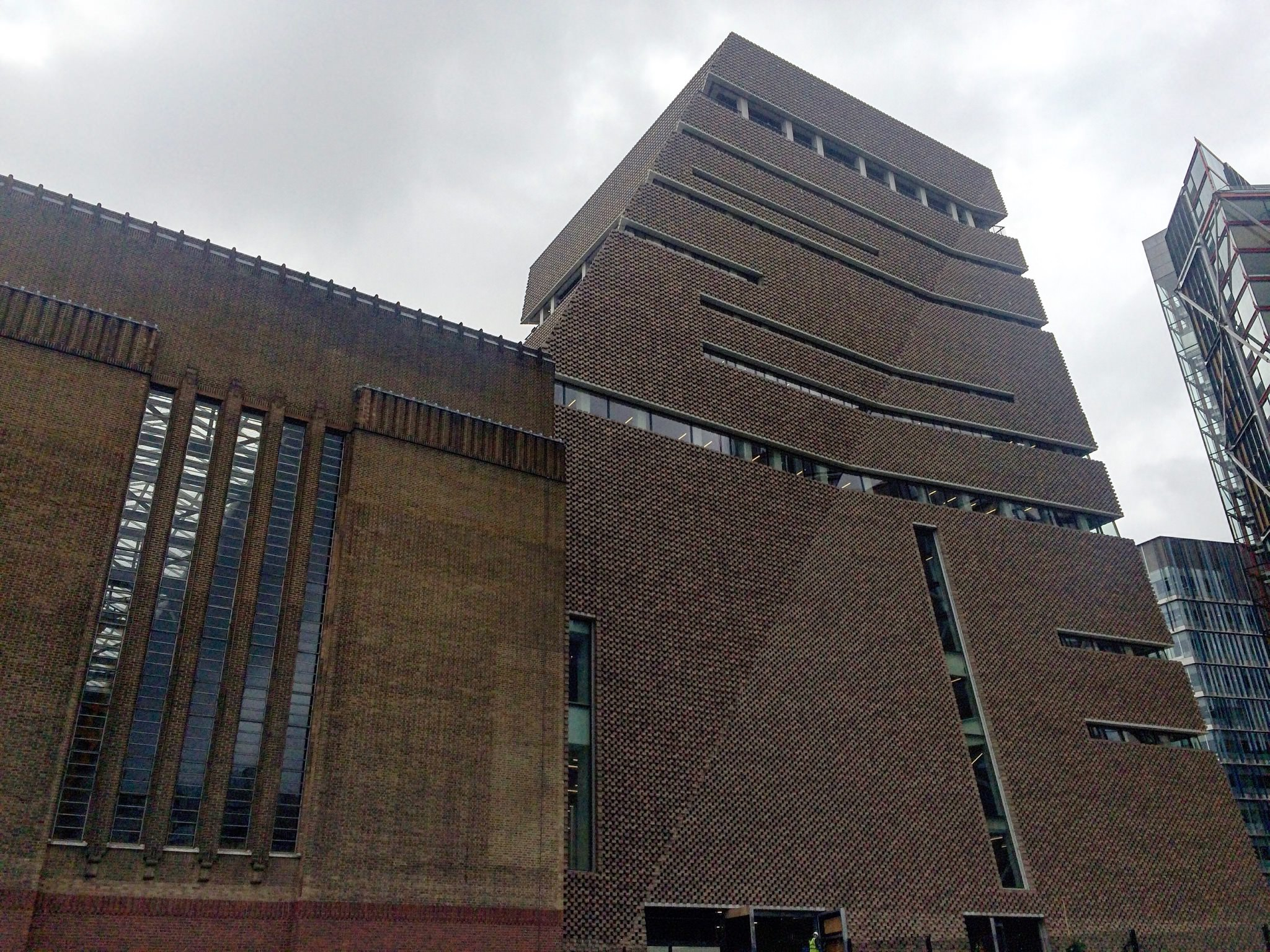 """Photo: Numéro   THE NEW TATE MODERN, BETWEEN STAR WARS AND BLADE RUNNER   Far from being a compacted bunker, the new wing is more like the monolith in 2001: A Space Odyssey. Its majesty evokes spiritual and religious monuments. Reaching into the sky, the building recalls the Tower of Babel, embodying a human culture determined to confront the gods. Or maybe a new Inca or Greek temple. It's certainly an edifice to the glory of Art, the new contemporary idol. But these backward looking references don't truly do this one-of-a-kind architectural object justice. A crooked object that seems to be in perpetual motion as if under the impetus of high-tech electronic mechanics transforming its appearance like a Rubik's Cube. The imagination convened on this site is pure science fiction. The new Tate Modern is a spaceship from the Star Wars Empire. Better than that, a building straight out Ridley Scott's Blade Runner.   """"The exterior shape of the building is as mysterious as it is confusing."""" Architect Jacques Herzog  At night fall the interior light escapes through the pierced façade accentuating our impression of being faced with an intergalactic cruiser. For Jacques Herzog, """"The exterior shape of the building is as mysterious as it is confusing and yet it results from a very rational geometric interpretation of the surrounding streets in the neighbourhood. The arising volumes remind us of a pyramid, but also a tent. It's open to interpretation."""""""