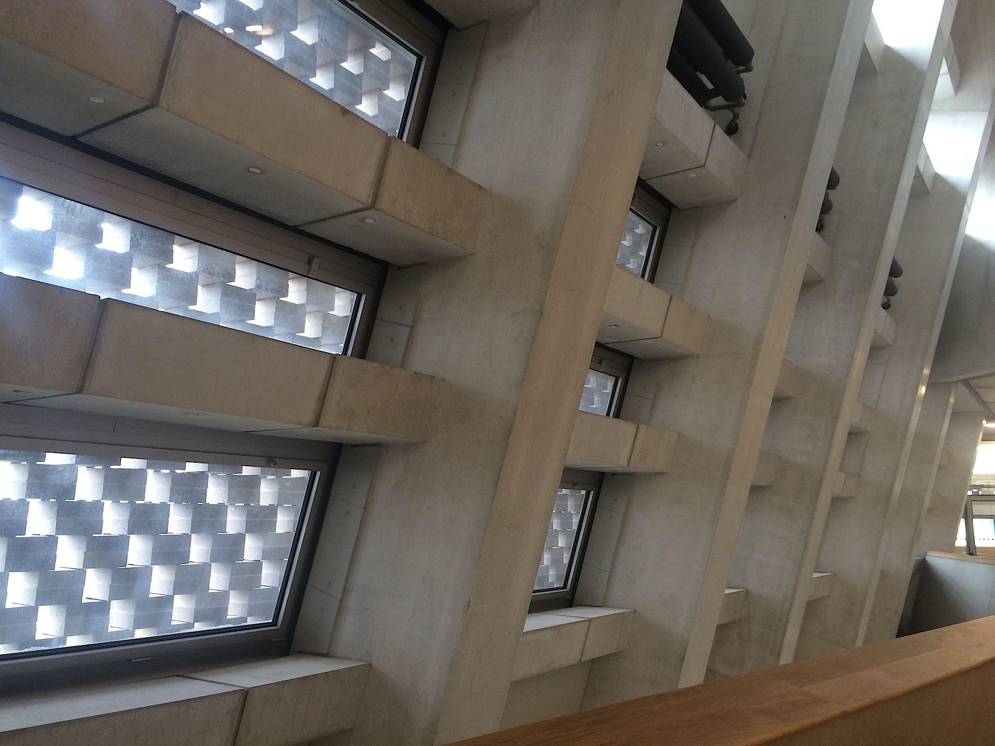 """Photo : Numéro   UNE PROMENADE ARCHITECTURALE ENTRE BOIS ET BÉTON   Cette nouvelle aile, entre béton brut et bois de chêne clair, offre des volumes vastes et ouverts particulièrement intéressants, notamment au niveau 2. Assez différents d'un étage à l'autre. """"La façade de briques est perforée de telle manière que la lumière du soleil peut entrer et adoucir la robustesse du béton, commente Jacques Herzog. La différence qui saute le plus aux yeux avec l'ancien bâtiment, c'est la gestion des flux. Au sein de la nouvelle aile, le public aura accès à une grande diversité d'escaliers et de rampes, qui créent une sorte de promenade architecturale, avec des bancs et des niches où l'on peut s'arrêter et discuter."""""""