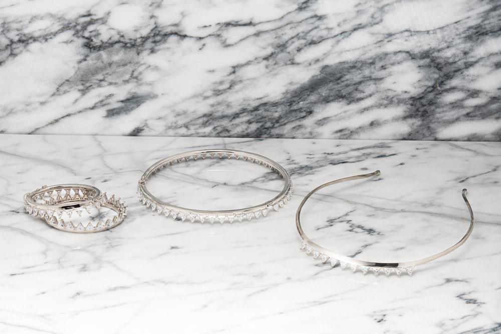 Eddie Borgo, collection automne-hiver 2016-2017.  Comment décririez-vous l'évolution de votre style au fil des années? J'ai abordé différentes inspirations en suivant ma passion pour les techniques et les formees. Mon fameux cône décliné dans différentes tailles, est inspiré du bijou touareg. J'ai réalisé pour Tilda Swinton un bracelet clouté à la main, et on m'a alors collé une etiquette de créateur rock'n'roll. Maus je pense que notre cliente attend en fait de nous des formes géométriques très pures et très simples, qui représente le glamour new-yorkais, inspiré de l'architecture de la ville. J'ai donc commencé à reconsidérer le langage de ma marque. A considérer les bijoux comme des sculptures miniatures.  Et vos sacs à main? J'étais très impressionné par les ateliers qui fabriquent nos bijoux en Italie, où le savoir-faire se transmet de génération en génération. Certains fabriquent également des sacs à main, et ces artisans me montraient toujours avec fierté des sacs qu'ils avaient réalisés dans les années 40 ou 50. Je me suis alors sérieusement penché sur ces formats oubliés, les doctor bags, pocket books, attaché cases. Même si l'offre en matière de sacs à main est pléthorique, il est difficile aujourd'hui de trouver ce type de format intemporel dans une gamme de prix abordable. J'ai donc eu envie de les proposer. Ces modèles respirent l'Amérique des années 50, ce glamour intemporel qui se construit dans la restreinte et une forme de modestie, avec une attention à la beauté de chaque détail. L'idée d'une construction rigoureuse est essentielle à ces formats qui relèvent presque de l'ingénierie. Ils sont équipés de poches pour iPhone, pour stylo, de fentes dans lesquelles glisser ses cartes. Je ne souhaite pas envahir le monde avec mes sacs. Aujourd'hui, j'aspire à rythme de croissance organique. J'ai compris qu'il ne sert à rien de tout anticiper et bousculer. J'ai envie de profiter de la vie et de voyager.   www.eddieborgo.com