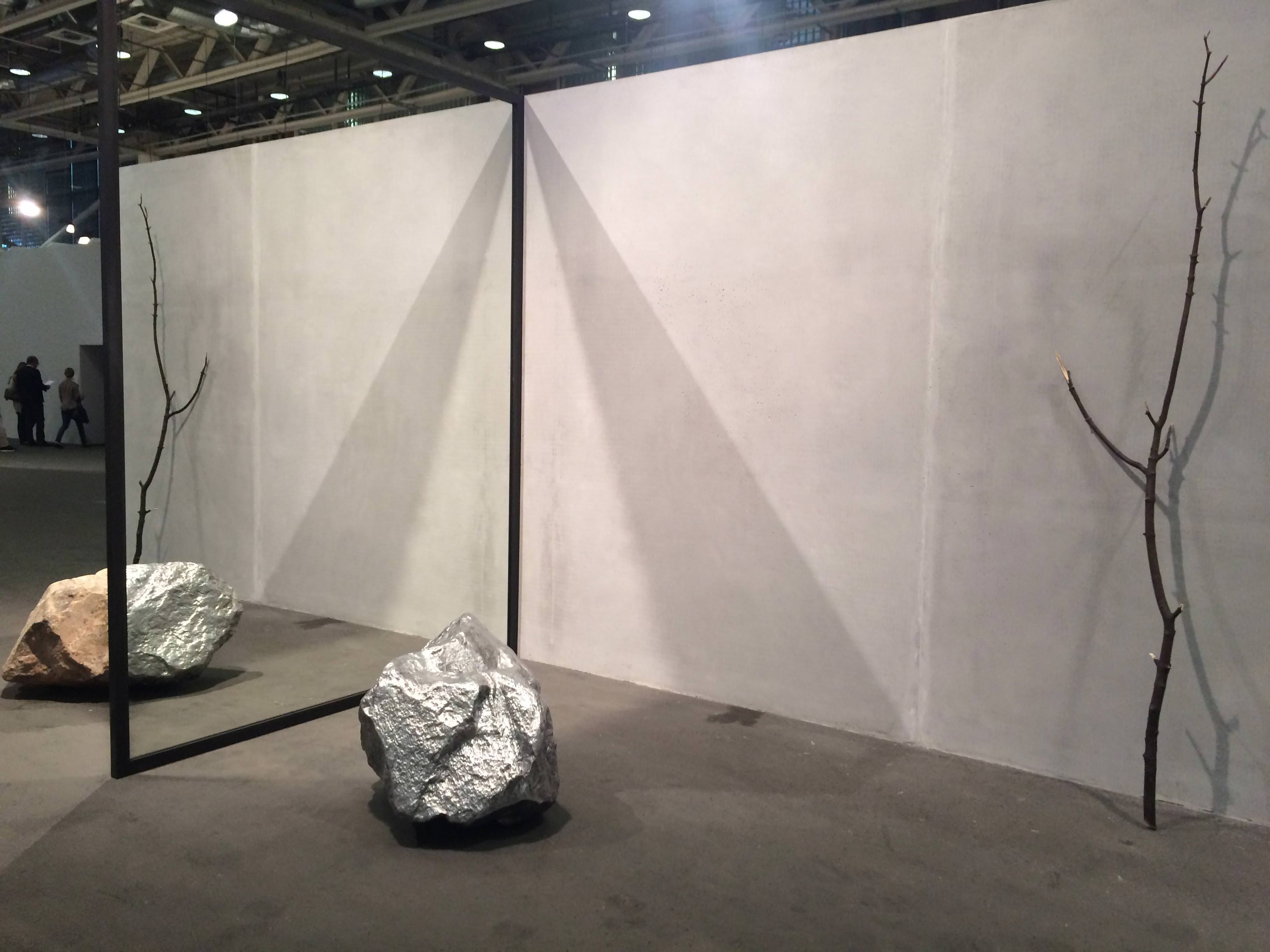 Out of Ousia(2016) by Alicja Kwade,303 Gallery, König Gallery and Kamel Mennour gallery.   A BIT OF POETRY IN A BRUTAL (CONCRETE) WORLD   We found poetry with Alicja Kwadeand her installation that plays with our perceptions in a game of mirrors. Depending on the perspective, a natural rock gets confused with its aluminium replica… Aged 37 the star status of the Polish artist, now living in Berlin, is confirmed, if it really needed to be. The same goes for Argentinian Pablo Bronstein,aged 39. His series of inks and watercolours on canvas proffer a panorama of imaginary and sinister Roman monuments, brilliantly combining baroque, antique, Viennese fin de siècle and 1930s inspirations.