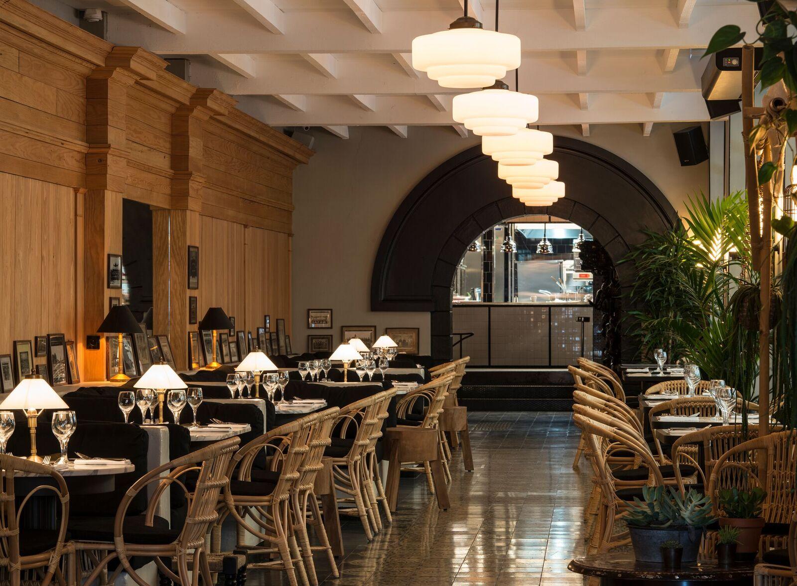 Le Sentier change de couleur. Après l'ouverture du bar à cocktails Le Fou, celle programmée du futur hôtel Hoxton juste en face, le restaurant Bambou, emmené par l'équipée de la Plage et du Très Honoré, fait son entrée dans un ancien dépôt de tissus du quartier. Branché thaï comme la cuisine, le décor imaginé par le duo Clément et Clémence Goutal (déjà à l'œuvre au Hibou de la place de l'Odéon), joue l'exotisme chic, sortant cages à oiseaux et dragon géant, canapés rouge carmin et ventilateurs en entrée. Pour dîner, réserver le salon et cabinet de curiosités aux collections de papillons et flacons d'apothicaires, ou l'une des banquettes-box sous lumière tamisée, le menu illustré sexy et dicté par le chef Antonin Bonnet (ex Sergent Recruteur) déclinant Hakao de crevette au lait de coco, satay de bœuf et soupes épicées parfaitement exécutées. Drink de fin de soirée recommandé au sous-sol où derrière la salle de billard américain s'ouvre un fumoir immense, lupanar parisiano-thaï éclairé d'une foule de lanternes. La maison tient aussi sa terrasse libérant ses vapeurs de fumées.   23, rue des Jeûneurs, Paris IIe. 0140 28 98 30.  www.bambou.fr