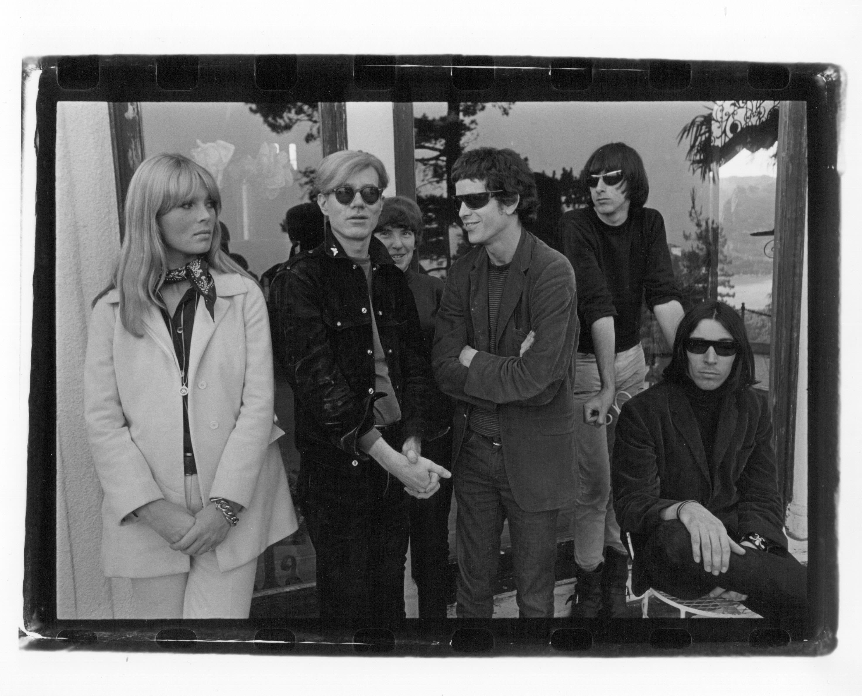 """Gerard Malanga, le Velvet Underground et Nico avec Andy Warhol, Hollywood Hills, 1966.Courtesy Galerie Caroline Smulders, Paris.  1.Elle fait sortir le Velvet de son statut underground Si l'influence du groupe formé par  Reed et John Cale au milieu des années 60 reste immense sur de nombreux courants comme le punk, la pop indé, le glam-rock et la new wave, leur nom reste moins culte que celui des Beatles ou des Stones. À l'époque, ils ont essuyé plusieurs échecs commerciaux, et n'ont connu le succès qu'après leur séparation. À l'occasion du 50e anniversaire de l'""""album à la banane"""" (enregistré en 1966 et sorti en 1967), cette exposition rappelle combien les chansons art rock-protopunk-expérimentales-psychédéliques du groupe étaient puissantes et majeures, grâce aux vidéos et au son intemporel diffusé tout au long du parcours."""