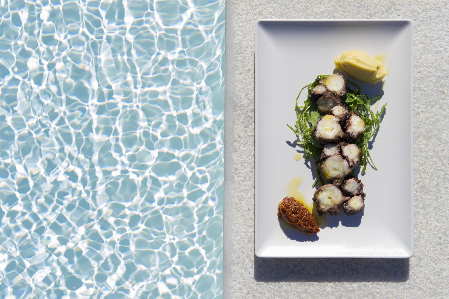 """Cuisine moléculaire et gastronomie bio  Loin des touristes qui s'amassent au nord de Mykonos, le restaurant Ftelia Bay propose une atmosphère apaisante et intimiste. La cuisine se veut gastronomique avec des touches moléculaires, chaque plat étant confectionné avec des produits biologiques venant directement du jardin de l'établissement ou de petits producteurs locaux, comme la """"Mousaka di mare"""" ou le """"Risotto aux figues"""". Une gastronomie mêlant produits du terroir et innovations culinaires.  www.fteliabay.gr"""