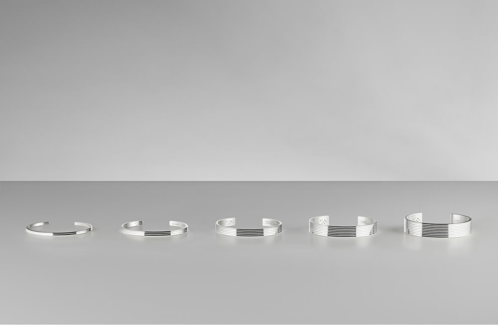 """Le Gramme, collection """"Guilloché horizontal"""".  Quelles sont les caractéristiques de votre forme élémentaire de bracelet? Les bracelets font 2 mm d'épaisseur (nous avons ensuite développé un modèle de 3 mm d'épaisseur pour un aspect plus massif). Ils ne sont pas moulés: nous partons d'un tube métallique, ce qui les rend plus qualitatifs. La fabrication 100 % française relève d'un mélange de production industrielle et artisanale: les formes réalisées en machine sont finalisées à la main.  La présentation des pièces en boutique semble faire partie intégrante de votre concept, pouvez-vous nous l'expliquer? Les bijoux sont enchâssés verticalement dans des supports unis ou marbrés, afin de dessiner une forme qui évoque une colonne vertébrale. Et le grand designer Martin Szekely nous a récemment fait l'honneur de dessiner un meuble vitré spécial, le """"VLG"""" (Vitrine Le Gramme), dans lequel nos créations seront désormais présentées."""