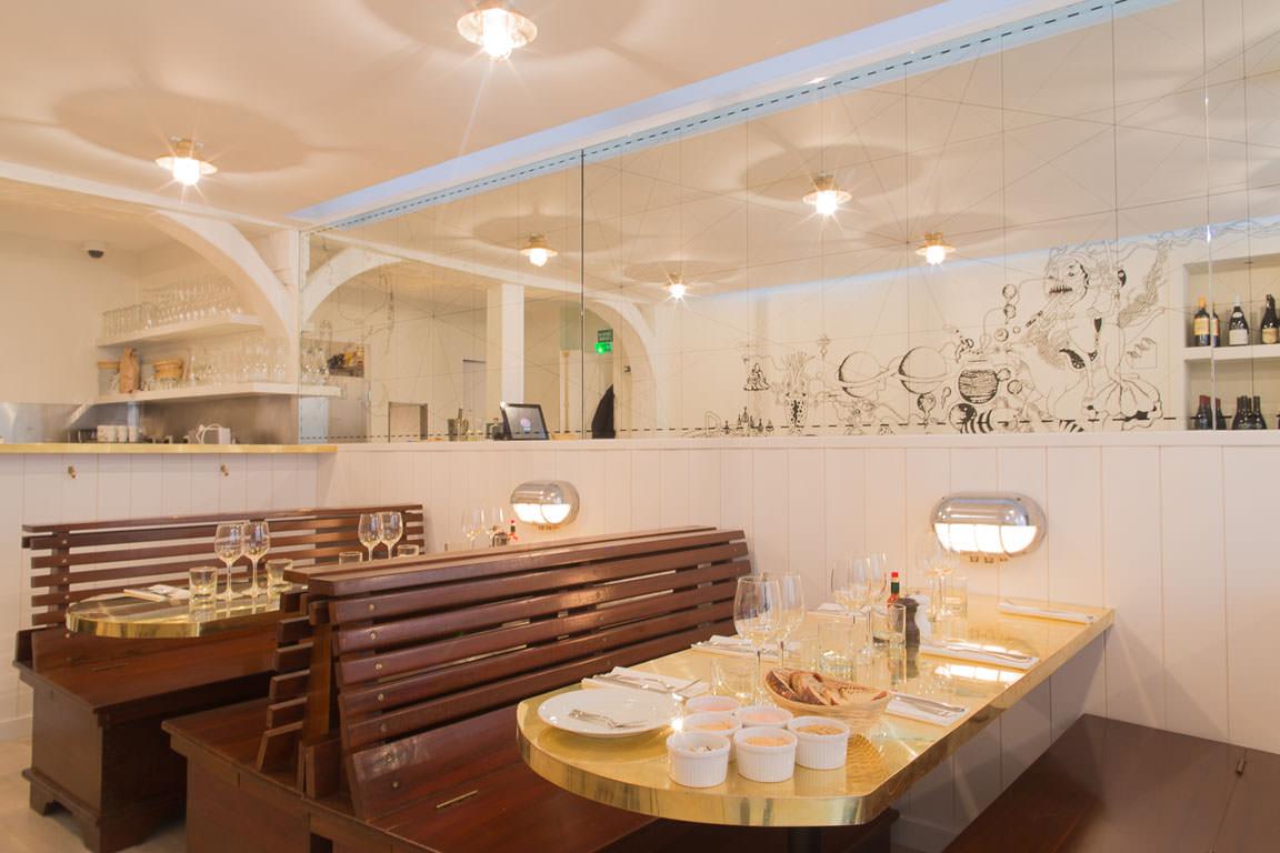 Lobster Bar  Demi-homard grillé ou façon hot-dog? Comme son nom l'indique, le Lobster Bar fait dans le mono produit. Ce petit restaurant ouvert en 2013 et situé rue Coquillère, importe un concept américain déjà bien établi outre-Atlantique.Arrangé à la sauce parisienne, les vins bios sont choisis directement chez le producteur, les huîtres de Bretagne livrées par l'ostréicultrice (pour les entrées), les homards originaires du Canada et les frites maison. C'est frais, c'est beauet bon.Passionné de bateau, Mathieu, le fondateur du lieu, a fait appel à des chasseurs d'antiquité pour trouver notamment ses banquettes-coffres en acajou massif ou ses appliques murales, provenant de cinq paquebots différents. Pour compléter la décoration singulière,une magnifiquefresqueaux personnages aquatiques du duo créatif Var, et un miroir gravé descôtesfrançaises et américaines.Savourer son homard, en profitant de l'ambiance et en écoutant Mathieu raconter ses histoires, là est la véritable expérience du Lobster Bar.  Lobster Bar 41, rue coquillère Paris I