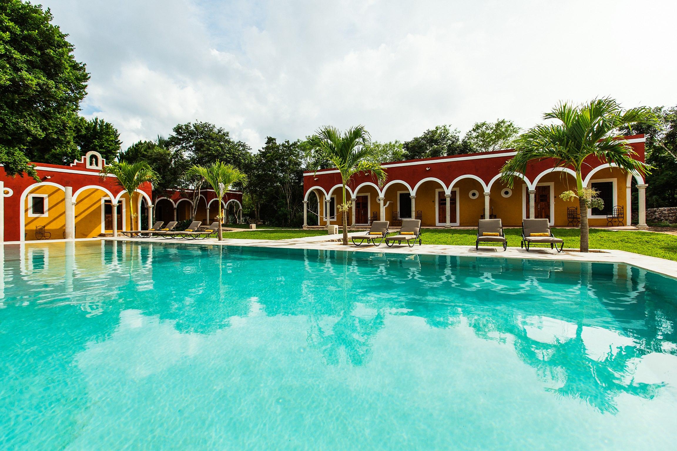 """L'Hacienda Ticum, ou Xcum, signifie en maya """"lieu du dieu de l'air"""". Établie en 1891, elle fut, dans une première vie,dédiée aux plantations de sisal –comme beaucoup d'haciendas de l'époque, dont les occupants produisaient à la main les cordes des naviresen défibrant une à une les tiges de la plante. Abandonnée ensuite dans les années 30, à l'époque de la réforme agraire du président Cárdenas, quandles terres furent redistribuées aux paysans, l'haciendatomba peu à peuen ruine. Seules les femmes de la chapelle du village voisin, Ekmul, continuèrent de veniry célébrer la sainte Croix et son saint, Santa Cruz."""
