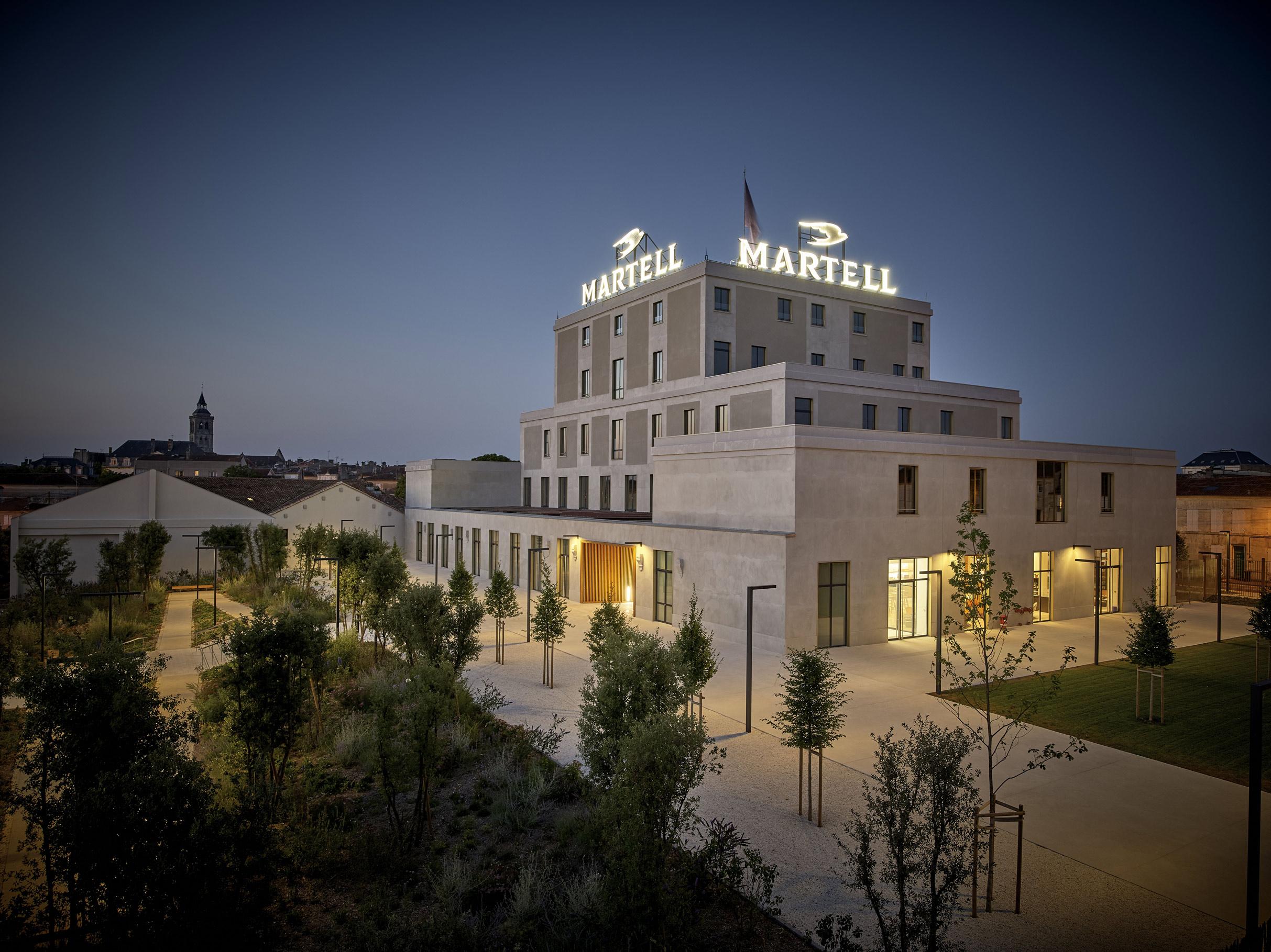 """©Philippe Caumes pour BLP   Un effet Martell à Cognac  Certaines leçons du fameux musée de Frank Gehry, qui avait dynamisé toute la région de la cité espagnole, ont été retenues. La fondation ne pourra animer son territoire qu'en s'y ouvrant. Physiquement déjà. Les travaux d'aménagement du bâtiment (qui auront lieu jusqu'en 2021) ont eu pour premier effet de détruire le mur qui séparait la ville de l'ancienne usine. L'œuvre gigantesque de Vincent Lamouroux, installée jusqu'à fin janvier au premier niveau, devient ainsi visible de la rue. Les habitants sont également invités à profiter des jardins intérieurs aménagés. Et le geste de l'artiste s'inscrit lui-même dans ce programme d'ouverture en s'appuyant sur les partenaires locaux de Martell.   Les vastes étendues de sable blanc du """"paysage"""" créé par Vincent Lamourouxproviennent du verrier Verallia. Le bois, de la tonnellerieLeroi. Une démarche qui semble avoir guidé,depuis l'origine, la commissaire d'exposition Nathalie Viot, qui confiait, lors de l'inauguration, avoir eu comme première préoccupation de rencontrer les salariés Martell ainsi que tous leurs collaborateurs de la région.   Un terrain de jeu global et local   """"L'ancrage local n'est en rien incompatible avec ouverture sur le monde et exigence artistique"""", renchérissait lors du vernissage César Giron, le P-DG de Martell Mumm Perrier-Jouët. Le choix de l'excellent artiste Vincent Lamouroux, lauréat du prix de la Fondation Ricard en 2006, et de la commissaire d'exposition Nathalie Viot, ancienne du célèbre Mamco de Genève, qui a également codirigé la Galerie Chantal Crousel à Paris, en est la preuve la plus flagrante et fait de la Fondation Martell un exemple d'institution """"glocale"""" (globale et locale à la fois).   La curatrice appelée à prendre la tête de la Fondation Martell et César Giron promettent une inauguration par étapes. Après la révélation de l'œuvre poétique de Vincent Lamouroux, les lieux fermeront pour travaux et rouvriront entre 2018 et 2021. """