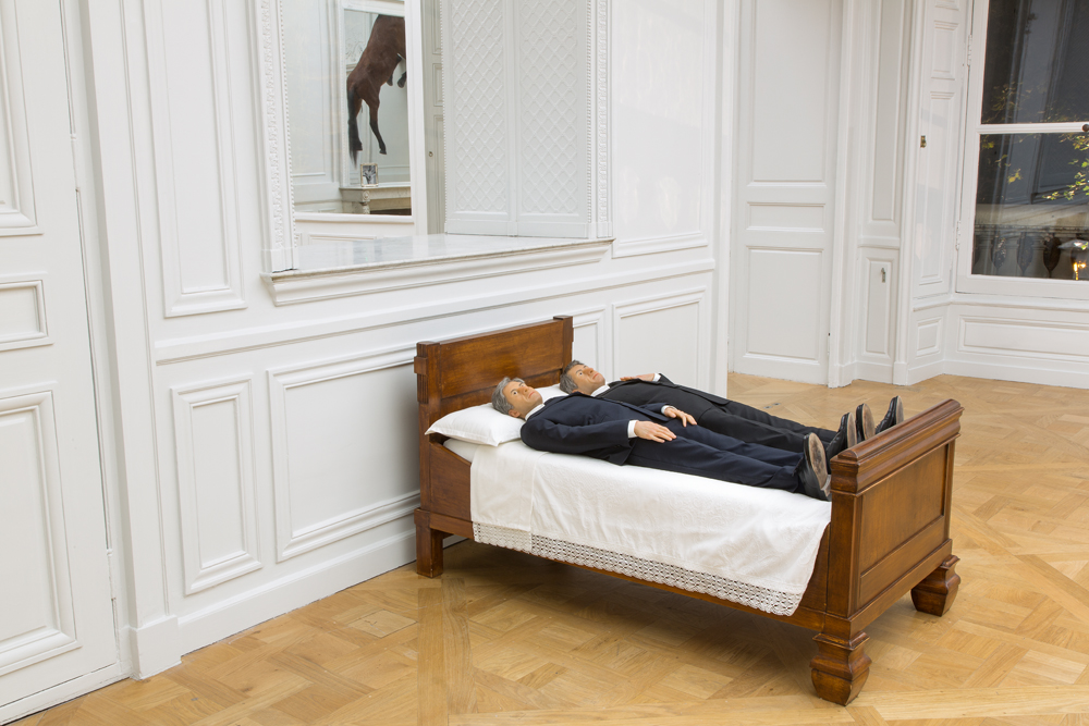 Foreground : Maurizio Cattelan, We, 2010 polyester resin, polyurethane, paint, human hair, clothes, wood Background : Maurizio Cattelan, Sans titre, 2007 Stuffed horse  Maurizio Cattelan, Lessico familiare, 1989 Black and white photograph, silver frame Photo : Zeno Zotti  View from Maurizio Cattelan exhibition, Not Afraid of Love at Monnaie de Paris, from october 21rst 2016 until January 8th 2017     Do you think that, in our world, we need to choke and provoke to make people think? I strongly believe that the only clever word is the one that chokes the throat. I'm pretty sure it's a senseless task to try to convey your idea to the audience: if something can be reduced to one clear concept, it is surely artistically dead.   You've frequently said that being an artist is just a job like any other. But after announcing your retirement five years ago, here you are again in the spotlight. Isn't it time to admit that art is a vocation? Why carry on making art? Tell me the truth: is this our first analysis session? Or have you decided it's not your vocation? Why do you persevere as a journalist? Isn't it time to accept that you should become a psychiatrist? Are we having a next session next week?