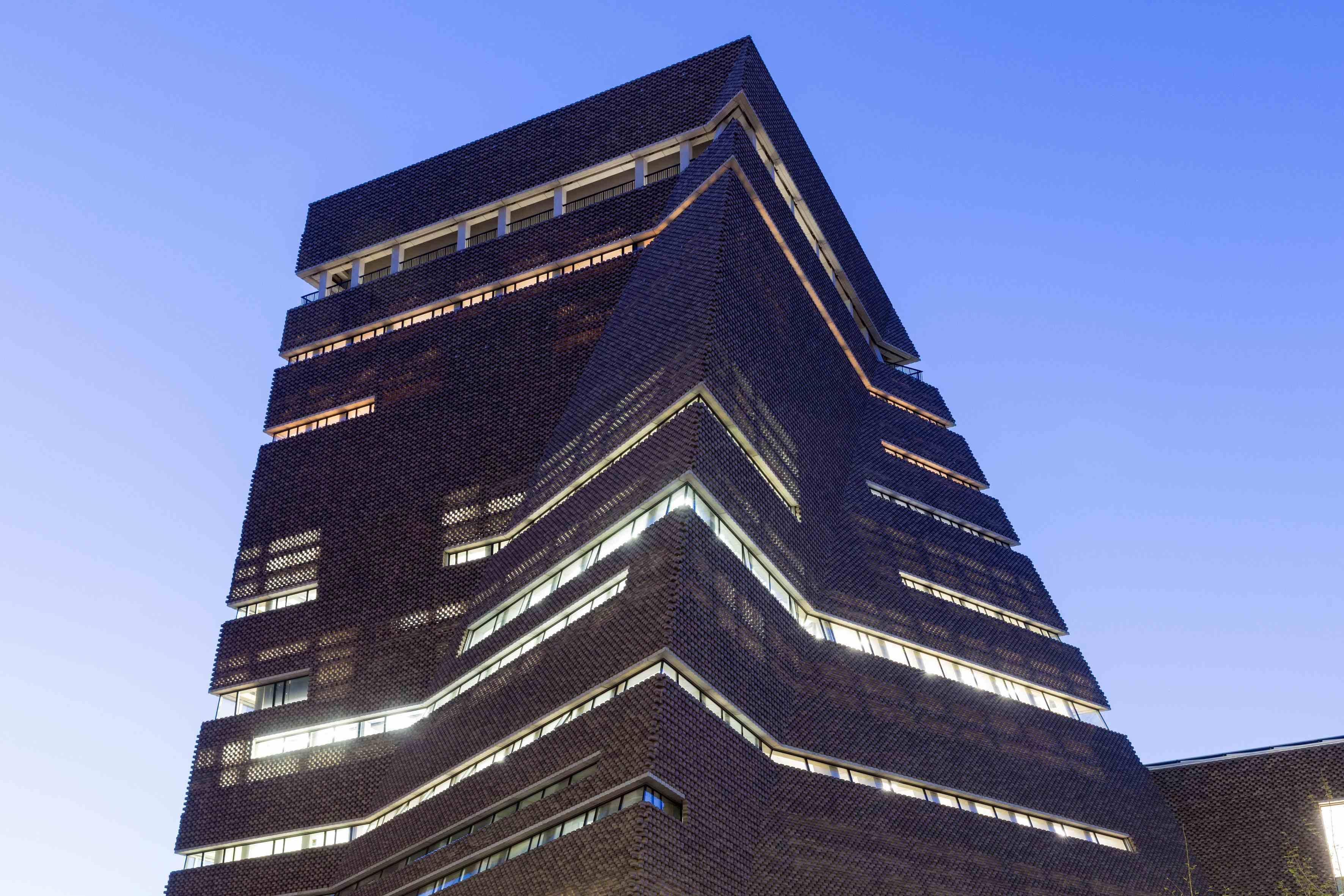 """© Iwan Baan   On est en 1995. Le duo d'architectes suisses Jacques Herzog et Pierre de Meuron remporte le concours visant à faire de la centrale électrique désaffectée dessinée par Giles Gilbert Scott un grand musée d'art moderne et contemporain pour Londres. Personne ne pouvait imaginer alors le succès de ce qui allait devenir l'une des plus grandes institutions mondiales: la Tate Modern. Les sceptiques raillaient l'objectif de 1,8 million visiteurs par an. Ils étaient 4,7 millions dès la première année d'ouverture en 2000. Ils sont plus de cinq millions aujourd'hui. En 2000 toujours, Herzog &de Meuron se voyaient récompenser du prestigieux Pritzker Prize, le Nobel de l'architecture. La messe était dite.   UNE CATHÉDRALE POUR L'ART   L'extension du musée qui a été présentée au public le 17 juin a, elle aussi, été conçue par le cabinet du célèbre duo bâlois. Depuis la Tate Modern, Herzog & de Meuron ont multiplié les réalisations muséales et se sont imposés en référence mondiale. Le San Francisco De Young Museum, l'extension du musée Unterlinden à Colmar, le Pérez Art Museum de Miami, l'extension du Walker Art Center de Minneapolis, la Schaulager de Bâle, le musée Blau de Barcelone… Autant dire que leur retour, vingt ans plus tard, sur le bord de la Tamise était (trop) attendu. Ont-ils pour autant déçu?    """"Ce bâtiment qui était autrefois le cœur battant de Londres en est aujourd'hui sa cathédrale culturelle.""""Lord Browne, président de la Tate     À écouter le président de la Tate, Lord Browne, pas vraiment. """"Ce bâtiment qui était autrefois le cœur battant de Londres en est aujourd'hui la cathédrale culturelle"""", s'enthousiasme-t-il devant un parterre d'invités, le mardi précédent l'ouverture officielle. Mais la tour de 64,5 mètres de haut et de 10 étages n'a pas que des adeptes. """"Trop déprimante!"""" On lui reproche l'obscurité de sa façade et le choix de briques (336 000 pour sa façade ajourée) qui ancre le bâtiment dans un passé industriel. """"Un véritable bunker!"""" On d"""