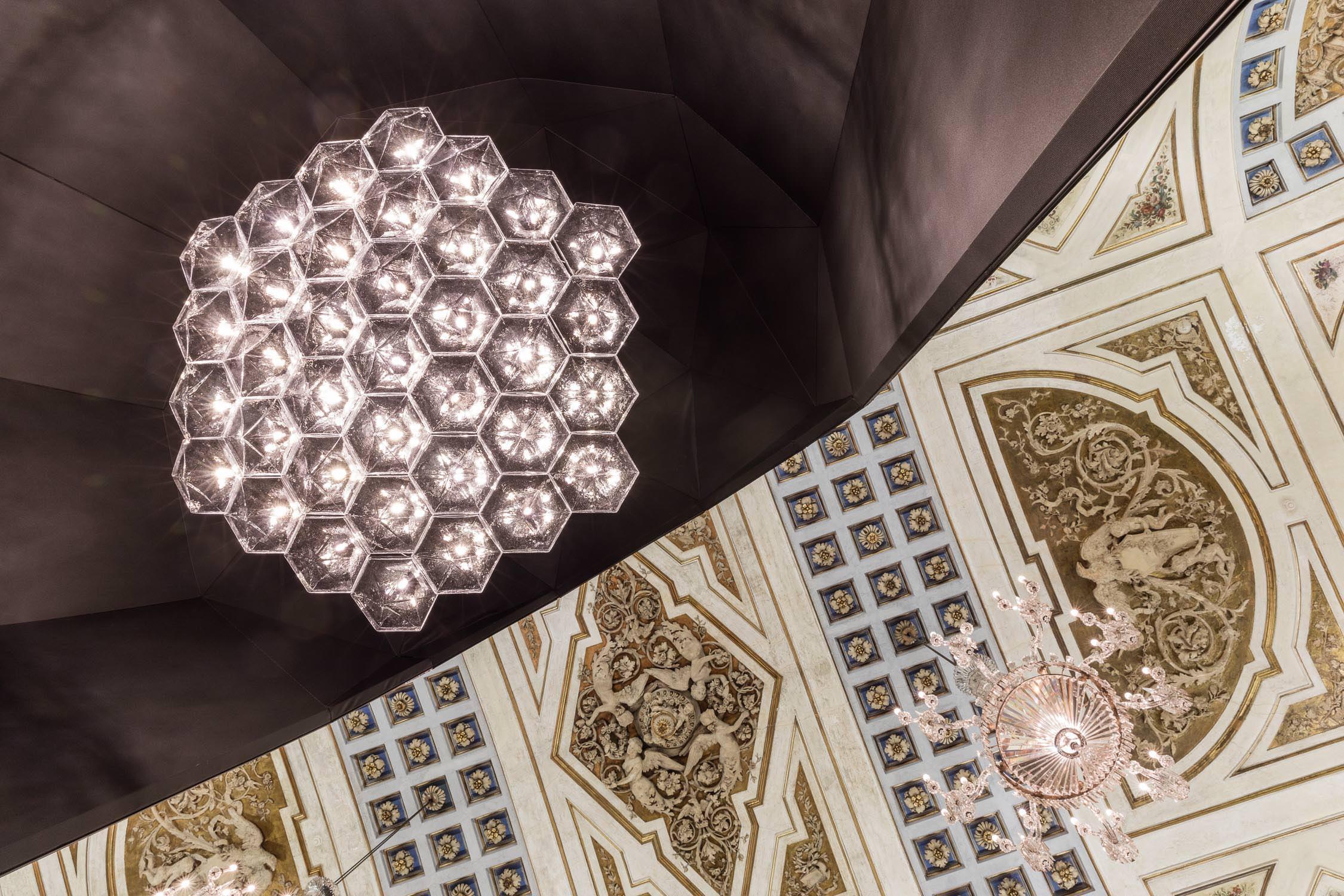 FACET deMoritz Waldemeyer  Avec FACET, Moritz Waldemeyer soumet le verre à sa volonté et donne vie à des structures modulaires régulières et organisées. Chaque module est utilisé seul en suspension ou combiné avec d'autres modules pour créer un grand lustre hexagonal dont la forme évoque celle d'un diamant. Moritz Waldemeyer a systématisé la fabrication de ce luminaire qui se distingue par sa clarté, sa rigueur et sa géométrie. Grâce à une source lumineuse intégrée à chaque module, ce système est universel et extensible à l'infini.