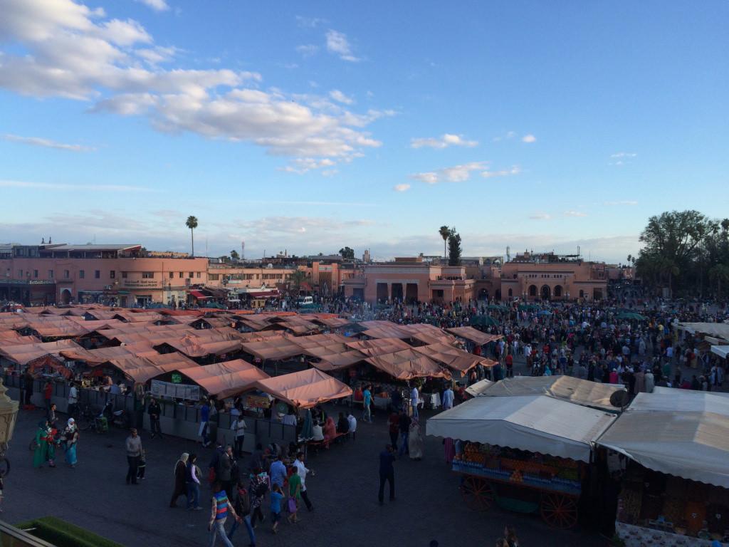 """La place Jemaa-el-Fna à Marrakech en pleine journée.    UN ART DE LA RUMEUR  Tino Sehgal, on ne le répètera jamais assez, c'est avant tout un art de la rumeur. Interdisant toute captation de son travail (photographique ou vidéo), l'artiste basé à Berlin alimente non seulement le mystère autour de son œuvre mais suscite surtout une rumeur travaillée par les récits oraux ou écrits qui en sont faits. Tino Sehgal prend volontairement à rebours notre époque où les concerts se vivent au travers d'un Smartphone et où l'image partagée instantanément est plus importante que l'expérience du réel. Il réactive aussi une manière de vivre prémoderne où les histoires sont contées avant d'être filmées et où les œuvres ne sont pas des objets physiques échangeables sur un marché de l'art insatiable. Ses œuvresjustement, qu'ilnomme""""situations"""", forment des moments chorégraphiés par ses soins où peuvent se mêler chants, danses, déplacements dans l'espace ou simples paroles. Un travail consacré, après avoir été présenté dans les plus grandes institutions du monde, par un Lion d'or à la Biennale de Venise en 2013."""