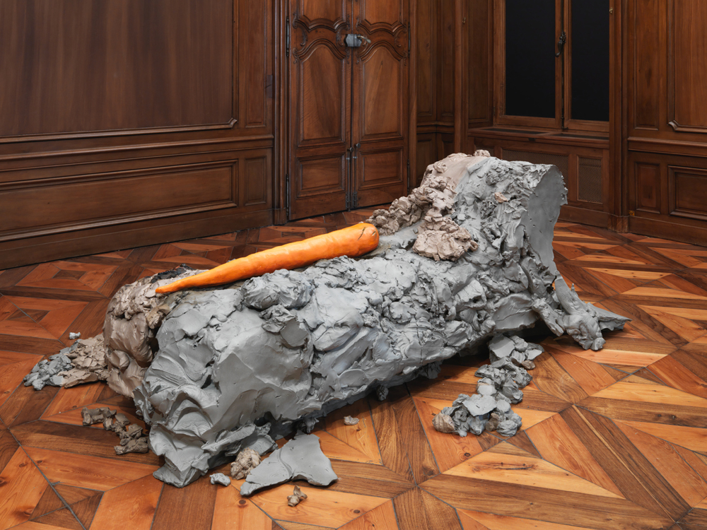 """Urs Fischer, 8(2014) bronze moulé, peinture à l'huile, feuille d'or, bol d'Arménie, apprêt acrylique, enduit à base de craie etcolle de peau de lapin. 78,7 × 215,9 × 199,4 cm. EA d'une édition de 2 & 1 EA. Collection privée. Avec l'aimable autorisation de l'artiste et de Sadie Coles HQ, Londres.    La dernière salle de votre exposition est recouverte d'un papier peint dont les motifs représentent des traces de peintures, tel la palette d'un peintre.  C'est un assemblage de différentes touches de couleurs dont j'ai photographié les mélanges sur une palette. Ces touches de couleur déposées sur la palette n'ont pas de véritable intentionnalité. Elles ne véhiculent pas d'information. Il n'y pas d'enjeu esthétique. La palette occupe depuis très longtemps une place importante dans l'histoire de l'art, et cela me plaît beaucoup.   Que dire alors des liens qui rattachent cette œuvre en particulier aux fameux coups de pinceau de la """"touche Van Gogh""""? Ils ont en commun un même aspect fragmentaire. Les coups de pinceaux de Van Gogh lui viennent de la gravure à l'eau forte. Ses lignes sont puissantes, et il imprime à chacune un léger soubresaut. La surface de ses peintures vous permet de ressentir la peinture elle-même.Il y a d'ailleurs une autre analogie possible avec Melodrama, qui pourrait être la représentation en 3D d'un tableau pointilliste."""