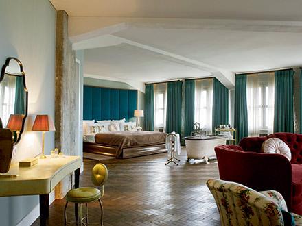 Passer derrière le rideau de fer  Séjourner dans un bâtiment du Bauhaus, ancien siège des archives du Parti communiste allemand, écouter du Ella Fitzgerald dans un lit d'époque, avec une baignoire au milieu de la chambre à coucher, en contemplant la vue imprenable sur tout Berlin-Est… le concept cartonne. C'est le Soho House. Damien Hirst a même contribué à la décora- tion du hall de l'hôtel.www.sohohouseberlin.com. © DR
