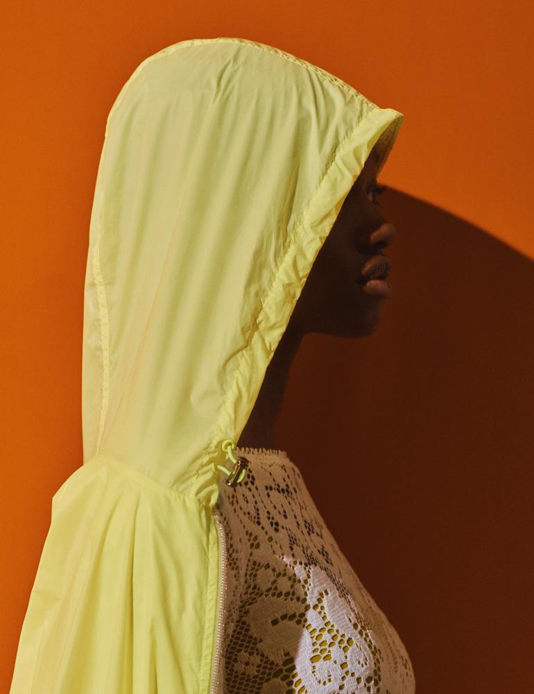 Manteau à capuche en Nylon technique, FILA. Robe en dentelle de coton, KRISTINA TI, portée sur un collant, WOLFORD.