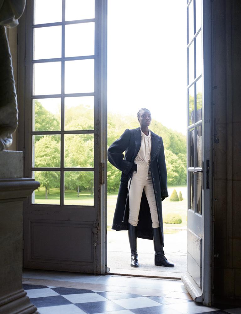 Manteau en drap de laine, Maison Margiela. Chemise en satin de coton, pantalon d'équitation en coton technique et bottes, Àcheval Pampa. Cravache, Hermès.