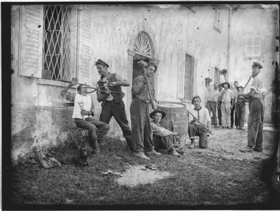 Roberto Donetta Scène apprêtée ; groupe d'hommes devant un bâtiment 1900-1932/1993 Tirage argentique sur papier baryté, virage au sulfure de sodium Photo 30 × 40 cm Musée d'art de la Suisse italienne, Lugano. Collection du Tessin