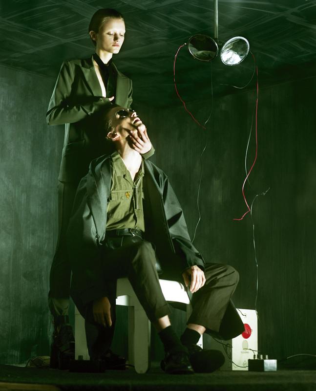Elle : veste et pantalon en gabardine de coton, PINKO. Cravate, ATSUKO KUDO. Chaussures, SACAI X PIERRE HARDY. Lui : trench en coton et soie, KOLOR. Chemise en coton, THE KOOPLES. Pantalon en coton, CERRUTI 1881. Ceinture, ZANA BAYNE. Lunettes, RAY-BAN. Collier, AMBUSH. Chaussettes, FALKE. Chaussures, PRADA.