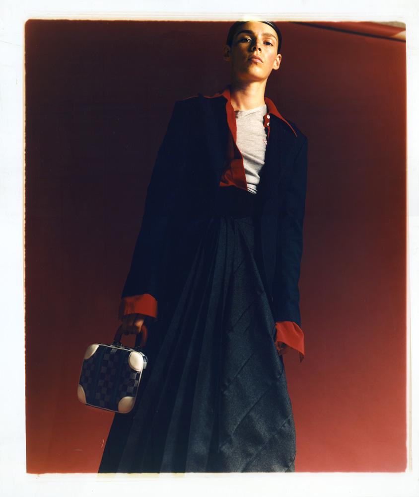 Veste en laine, CÉDRIC CHARLIER. Chemise en soie, VICTORIA BECKHAM. Tee-shirt en coton, GUESS. Jupe plissée en laine, MARNI. Bibi et sac, LOUIS VUITTON.