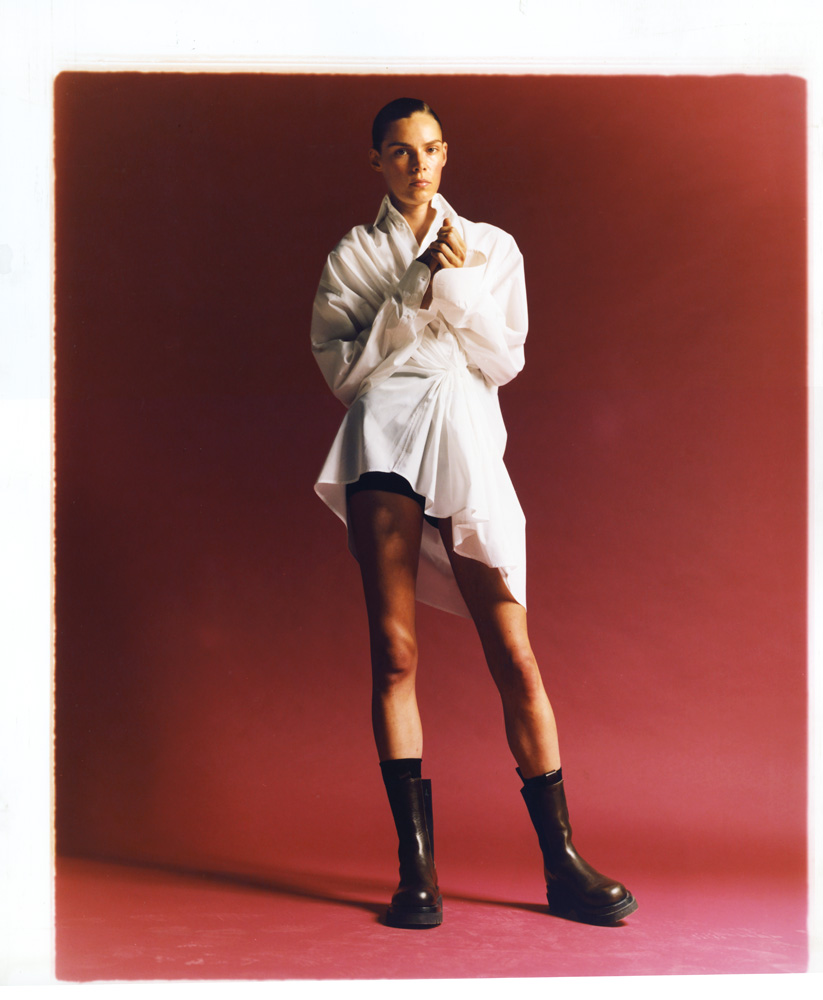Chemise oversize drapée en coton, OLIVIER SAILLARD, MODA POVERA. Short en laine, MIU MIU. Chaussettes, FALKE. Bottes, BOTTEGA VENETA.