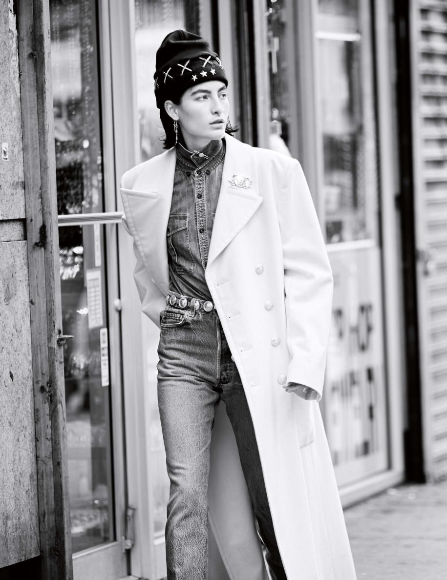 Long manteau en cachemire, CHANEL. Chemise et jean en denim, GUESS. Bonnet, FENTY PUMA BY RIHANNA. Pin's et broche, NEW YORK VINTAGE. Ceinture vintage, VERSACE CHEZ DEPUIS 1924. Boucles d'oreilles vintage.