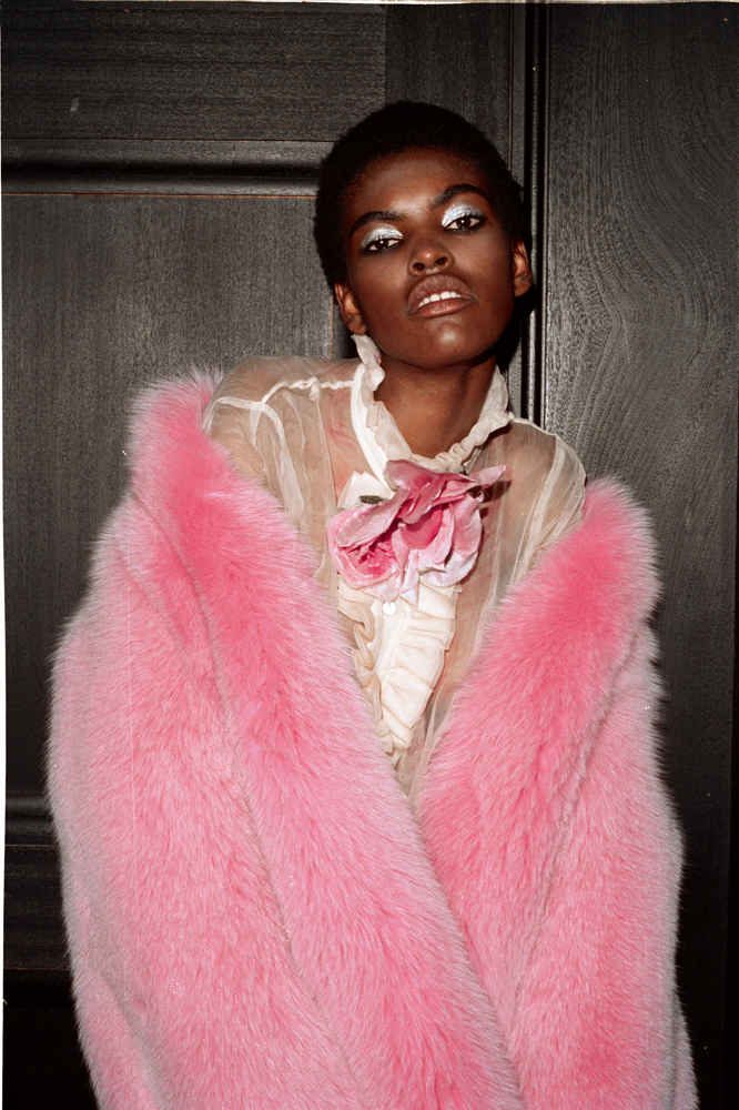 Veste en fourrure, blouse à jabot en organza et broche, GUCCI. Escarpins : SAINT LAURENT.