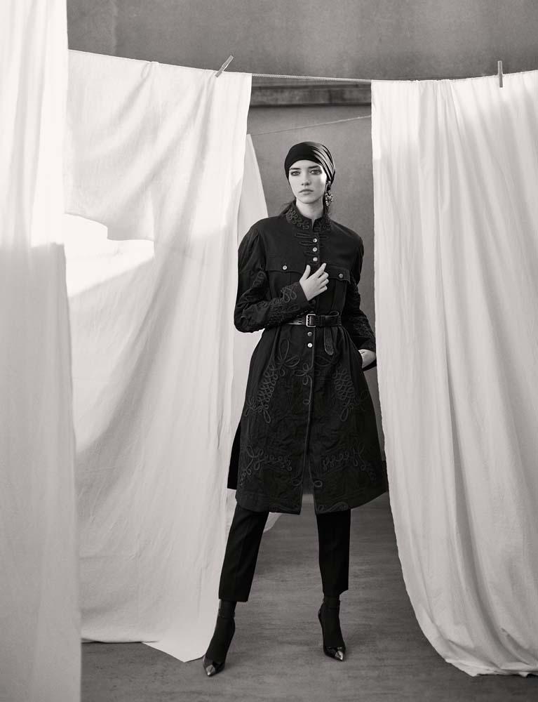 Manteau en coton à passementeries, DRIES VAN NOTEN. Pantalon en crêpe, ceinture, boucle d'oreille et chaussures, SAINT LAURENT PAR ANTHONY VACCARELLO.