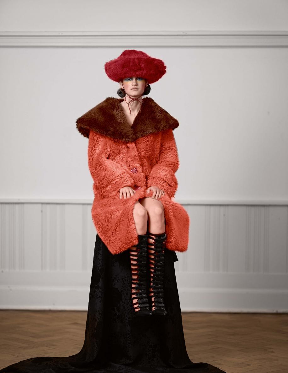 Manteau et chapeau en fausse fourrure, MIU MIU. Bottes, J.W. ANDERSON . À droite : manteau en cuir à franges et broderies de perles, jupe en laine et plumes d'autruche, et écharpe, PRADA. Boucle d'oreille, GOOSSENS PARIS.