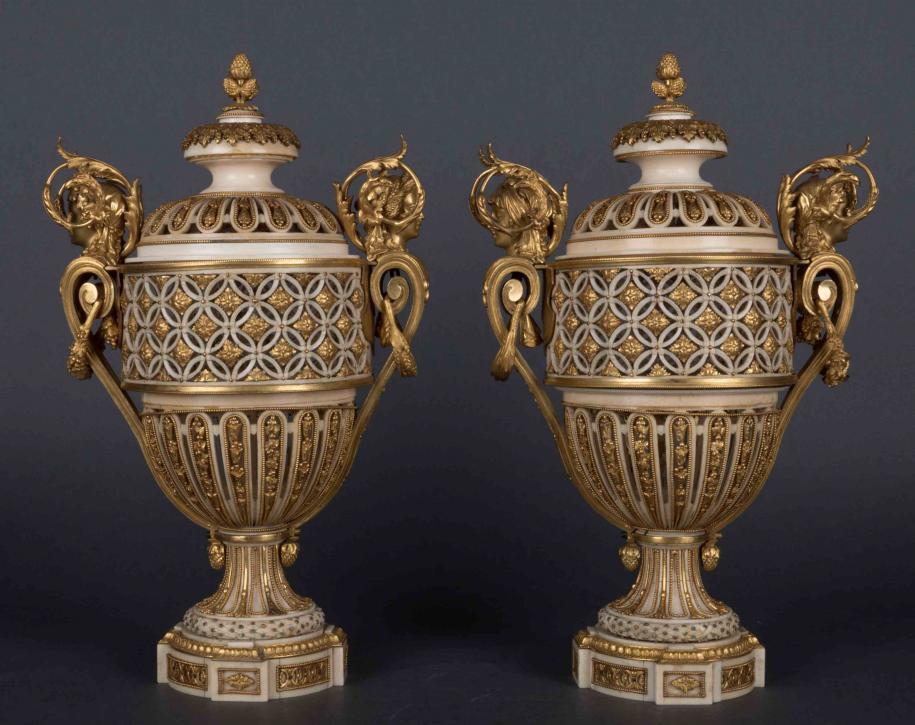 Paire de vases en ivoire à monture de bronze doré d'époque Louis XVI. Le travail de l'ivoire est attribué à François Voisin et les montures en bronze ornées de têtes de femme représentant le printemps et l'été sur un vase, l'hiver et l'automne sur l'autre, sont attribuées à Pierre Gouthière.