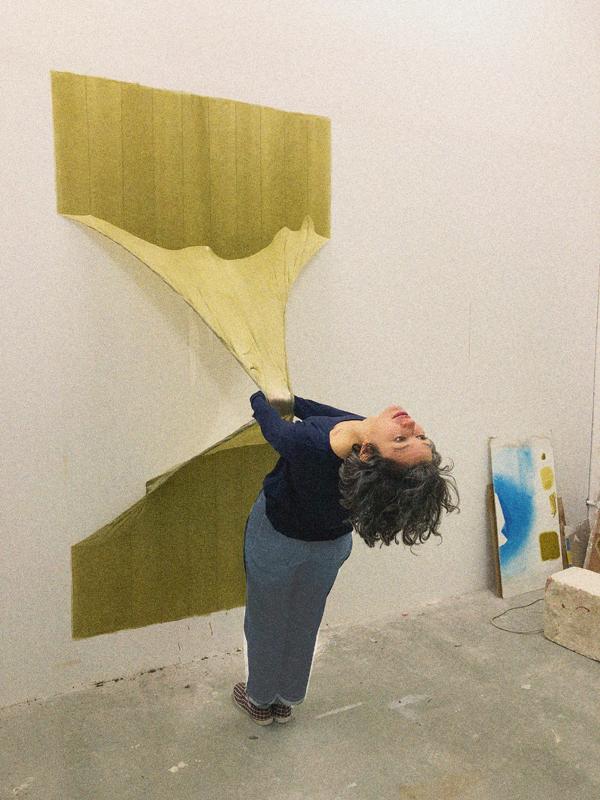 L'ARTISTE ELENA DAHN AGRIPPÉE À L'UNE DE SES SCULPTURES-PEINTURES EN LATEX.