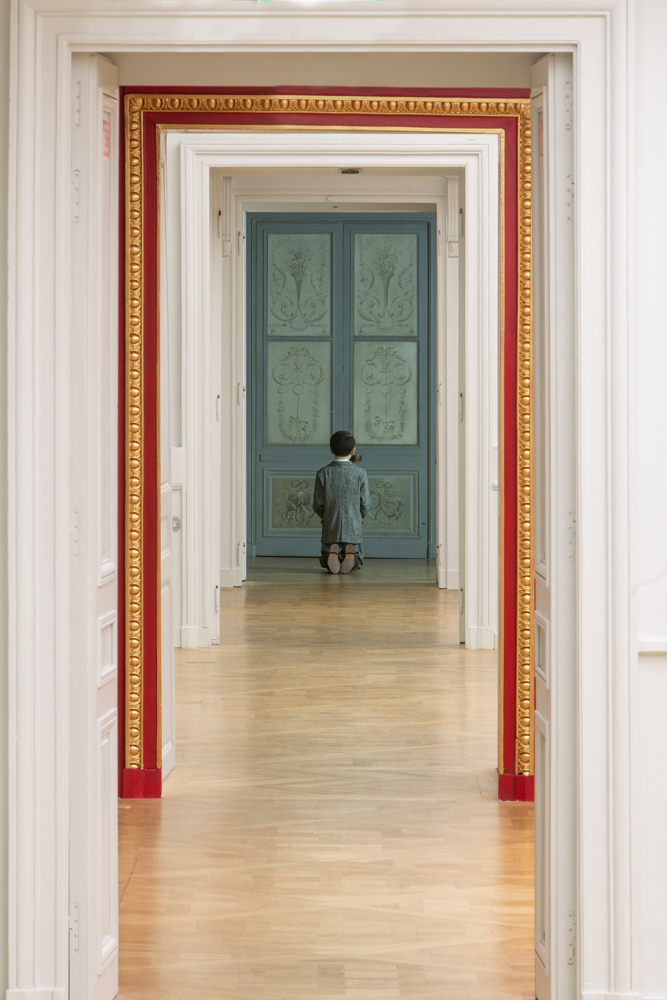 Maurizio Cattelan, Him, 2001  Résine polyester, cire, cheveux humains, vêtements, chaussures  Photo : Zeno Zotti  Vue de l'exposition Maurizio Cattelan, Not Afraid of Love à la Monnaie de Paris, du 21 octobre 2016 au 8 janvier 2017