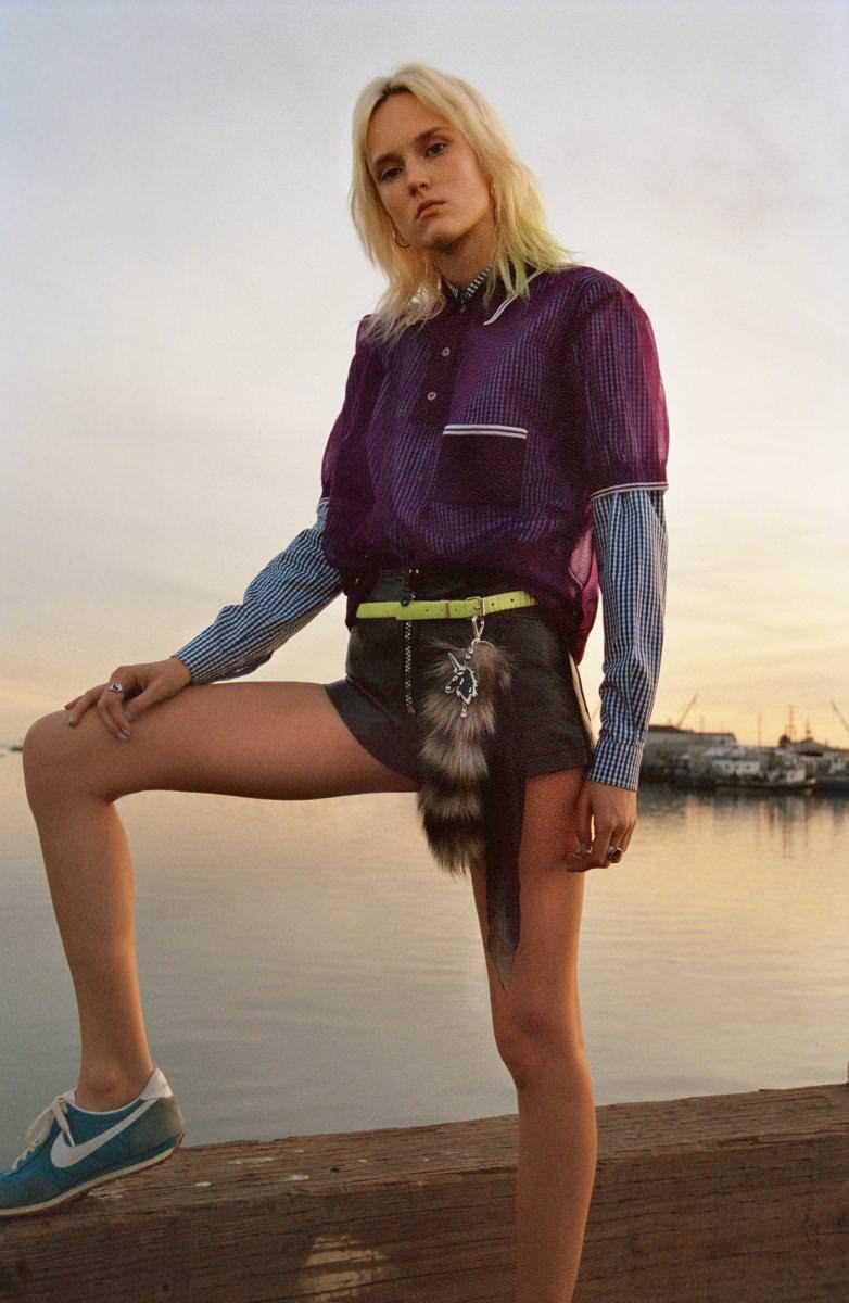 Polo en Nylon, chemise en coton et pendentif en fourrure, MIU MIU. Short en cuir, DIESEL. Ceinture, FUNKYTOWN. Boucles d'oreilles, CARTIER. Bagues, SEARCH & DESTROY. Baskets vintage.