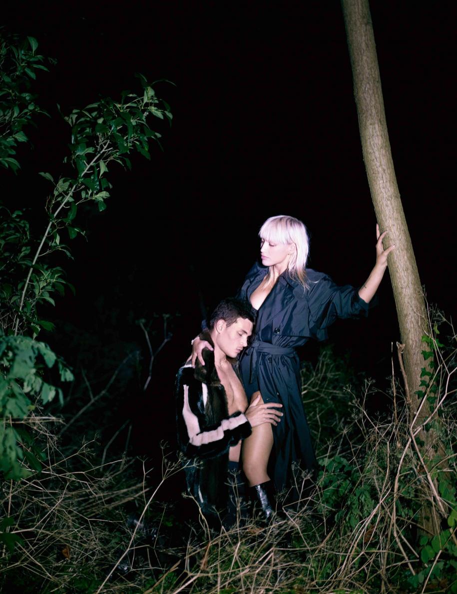 Lui : blouson en vison et pantalon en gabardine de laine, Fendi. Boots, Doursoux. Elle : trench en Nylon, Versace. Bottes, Saint Laurent par Anthony Vaccarello.