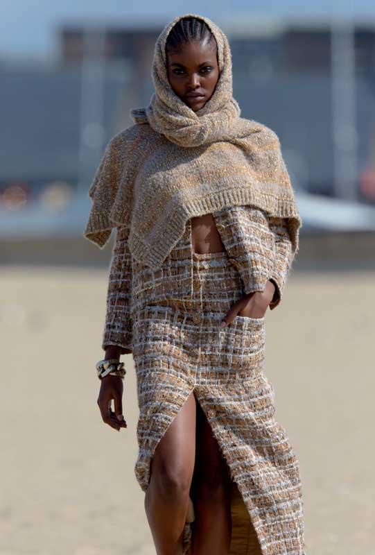 Robe en laine portée en étole, veste et jupe en tweed pailleté, CHANEL. Bracelet, SAINT L AURENT PAR ANTHONY VACCARELLO.