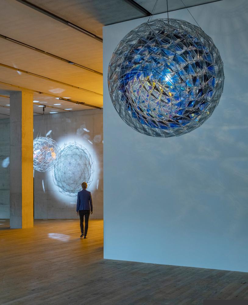Vue de l'expositionIn Real Lifeà la Tate Modern, Londres, 2019 avec l'oeuvre : Olafur Eliasson,Cold wind sphere(2012), Acier inoxydable, verre teinté (bleu sombre, bleu et vert clair), miroir, filtre de verre (bleu), bulbe, Diamètre : 170 cm.Collection du Centre Pompidou, MNAM-CCI, Paris /© 2012Olafur Eliasson / Photo : Anders Sune Berg