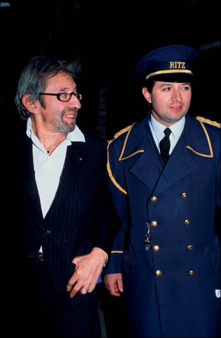 Serge Gainsbourg, coutumier des bars de l'hôtel, posant avec un portier en 1991. CourstesyARNAL/Gamma-Rapho/Getty Images.