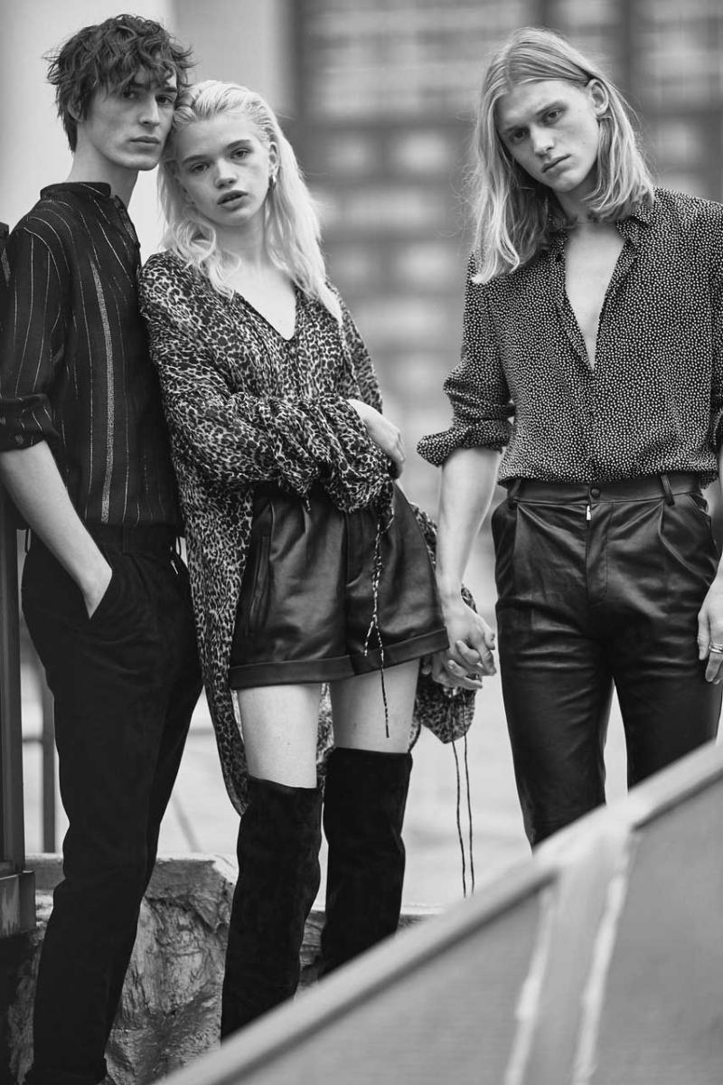 From left to right, him: cotton and Lurex shirt, and jeans, SAINT LAURENT PAR ANTHONY VACCARELLO. Her: printed silken blouse, leather short and thigh boots, SAINT LAURENT PAR ANTHONY VACCARELLO. Him: printed silken shirt and leather trousers, SAINT LAURENT PAR ANTHONY VACCARELLO.