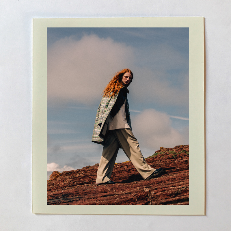 Manteau en toile de coton imprimée, BURBERRY. Chemise en cuir et pantalon en laine, CÉLINE. Chaussures, DR. MARTENS.