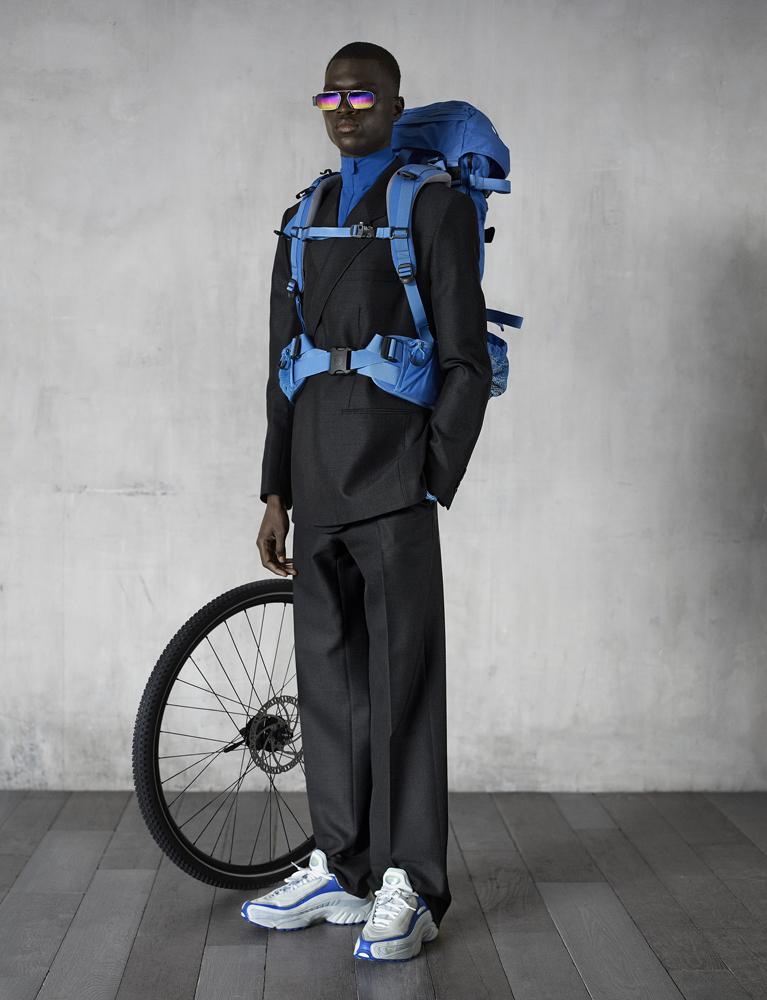 Costume croisé en drap de laine et lunettes, Dior. Parka en Nylon (en dessous), Aeance. Sac à dos, Fjällräven. Baskets, Reebok. Roue de vélo, Genesis.