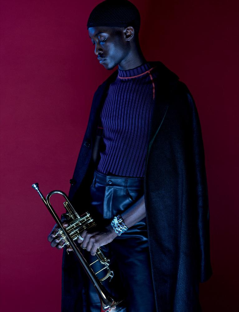 Manteau en lin, pull en coton technique et pantalon en cuir, Salvatore Ferragamo. Collier (au poignet), Louis Vuitton. Trompette, Advences.