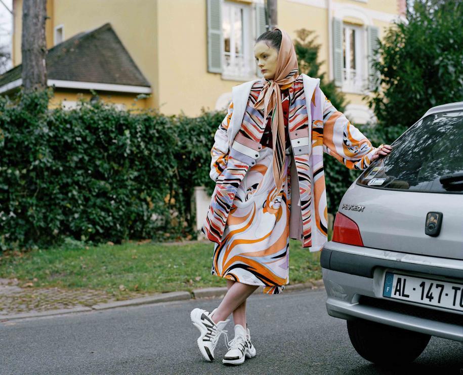 Manteau à capuche et robe portée en jupe en éponge, EMILIO PUCCI. Veste ceinturée en fourrure de veau et foulard, LONGCHAMP. Baskets, LOUIS VUITTON. Bagues, AMBUSH. Bague, VERSACE. Bague, CHARLOTTE CHESNAIS. Bague, SONIA RYKIEL.