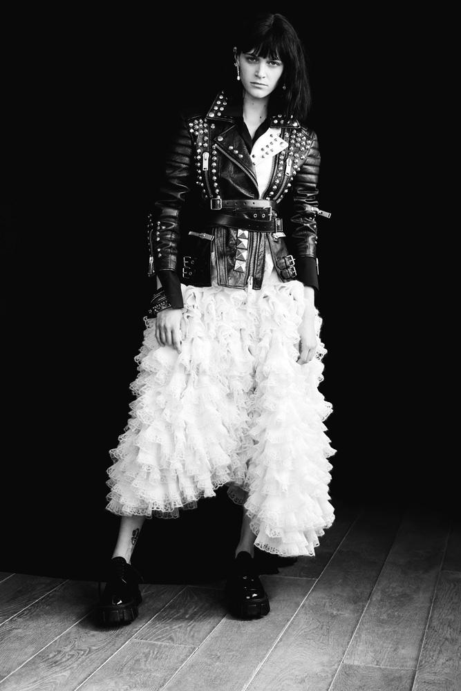 Blouson bicolore en cuir clouté, jupe volantée asymétrique en soie etmohair,etceinture,ALEXANDER MCQUEEN. Boucles d'oreilles haute joaillerie en platine et diamants, CARTIER. Bracelets, TOBIAS WISTISEN CHEZ MAD LORDS. Chaussures, PRADA.