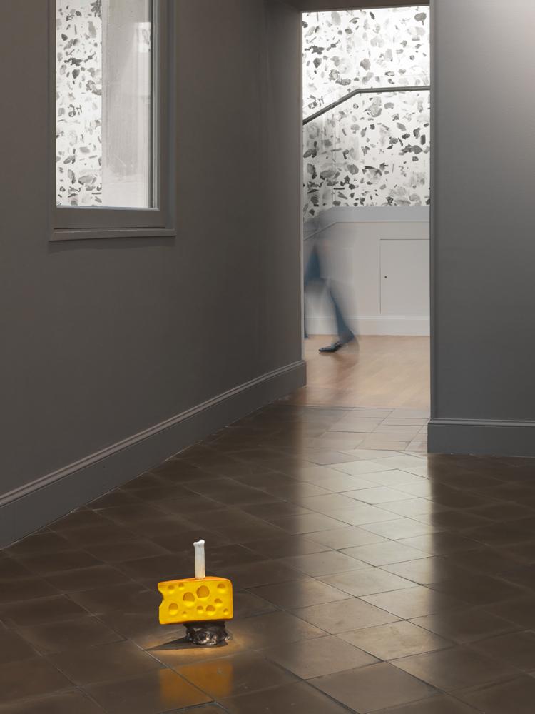 """Urs Fischer, Happy Cheese(2016), bronze moulé, apprêt acrylique, enduit etpeinture à l'huile. 23,2 × 16,5 × 13,2 cm. EA 2 d'une édition de 2 & 2 EA. Collection privée. Avec l'aimable autorisation de l'artiste,Gagosian Gallery,Sadie Coles HQ, Londres.   Dans un couloir, vous avez posé au sol une sculpture intitulée Happy Cheese. En quoi l'association bougie+fromage forme-t-elle un """"joyeux fromage""""? J'ai d'abord réalisé le fromage, et j'avais envie de poser quelque chose dessus. Je voulais qu'il ressemble à une part de gâteau, donc je lui ai mis une bougie. C'est une sorte de gâteau d'anniversaire, même si, dans cet exemple, la bougie n'est pas à la bonne échelle pour une bougie d'anniversaire.   Cela me rappelle les œuvres de Robert Gober autour de la cire et du fromage – un artiste que vous avez d'ailleurs exposé à l'occasion de False Friends,exposition collective qui rassemblait des œuvres de la Fondation DESTE au musée d'Art et d'Histoire de Genève. J'aime beaucoup son travail, mais il relève d'une psychologie différente. Dans son œuvre – pour autant que j'en comprenne les mécanismes – il y a toujours une dimension reliquaire, comme une trace laissée par quelque chose qui a existé ou qui a eu lieu. L'absence d'une situation qui s'est déjà produite, comme dans un film noir."""