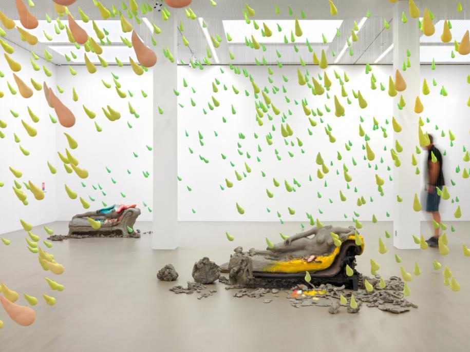 Vue de l'installation Melodrama(2016). Collection Maja Hoffmann/LUMA Foundation. Avec l'aimable autorisation de l'artiste et de Sadie Coles HQ, Londres.     Pourquoi avoir choisi d'associer deux papier peints différents, l'un en noir et blanc, l'autre en couleurs? Pour structurer l'espace. Et accorder un peu de «répit» après cette explosion de couleurs.   Il y a aussi un four à micro-ondes posé sur le sol. Le bacon qu'on y a fait cuire diffuse son odeur dans l'exposition.  Je cherchais à établir un lien avec les motifs du papier peint. J'ai travaillé pour cela avec un parfumeur, afin de créer une odeur qui mélange le bacon à l'essence de térébenthine. Mais elle ne sentait pas aussi bon que les vraies odeurs prises séparément. J'ai donc décidé d'utiliser simplement l'odeur du bacon.   Sur le papier peint, vous avez posé une série d'œuvres en aluminium, aux motifs de personnages de dessins animés.  J'ai commencé par faire des petites choses pour ma fille, des découpages d'animaux. Et là, je me retrouvais avec des formes et des découpes particulières, des fragments. J'ai utilisé des images de petits cochons piochées au hasard sur internet. Il y a systématiquement une ligne qui vient diviser tous ces personnages en deux parties.