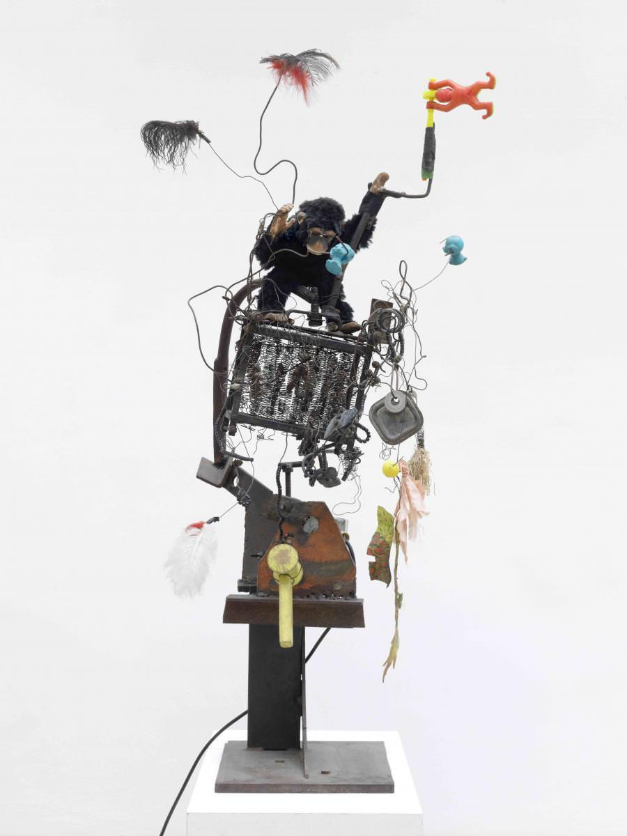 """Jean Tinguely,Wackel-Baluba(Catalogue Raisonné n°338),1963 Socle en acier, barres de fer, ressorts et fils électriques, jouets en plastique, plumes, singe en plastique, moteur électrique 220 volts.126 x 40 x 64 cm / 49 5/8 x 15 3/4 x 25 1/4 in. Courtesy NCAF et Galerie GP & N Vallois, Paris Photo: André Morin   Preuve est faite qu'un artiste mort peut encore bougeret faire du bruit chez Georges-Philippe et Nathalie Vallois. À l'occasion du 25e anniversaire du décès de Jean Tinguely, la galerie a décidé de rendre hommage à cet artiste majeur du XXe siècle en présentant une quinzaine de ses sculptures et reliefs animés. Ça tourne et ça grince… Ça évoque surtout un jubilatoire chaos dionysiaque et anarchiste. L'exposition qui réunit des œuvres des années 60 – la période des expérimentations libres de celui qui fut l'une des figures du Nouveau Réalisme – est digne d'un musée, si ce n'est que sa vitalité (les """"bing"""", """"bong"""", grincements et mouvements) la rend bien trop vivante pour une quelconque institution classique.    """"La légende veut que ce soit le père de Jean Tinguely qui ait appelé lui-même les pompiers."""" Nathalie Vallois"""