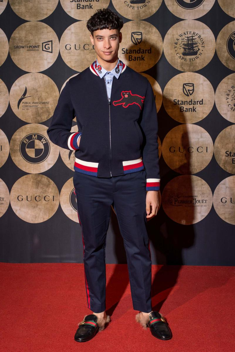 Jody Paulsen wore a Gucci Pre Fall 2017 navy bomber jacket with white, red, and blue web and an embroidered panther, blue cotton pants with bordeaux web, white pin-point duke shirt with collar embroidery, and a black leather princetown shoes with web, GG detail and natural fur.